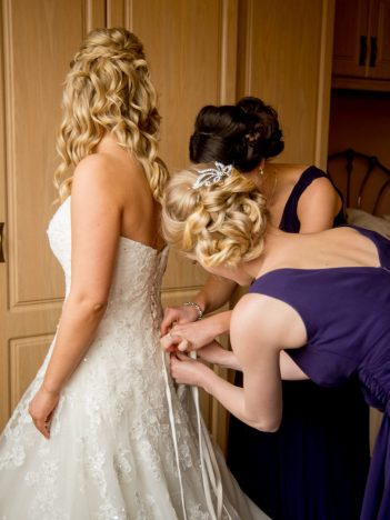 A bride in a corset wedding dress that is being done up by 2 bridesmaids in purple dresses