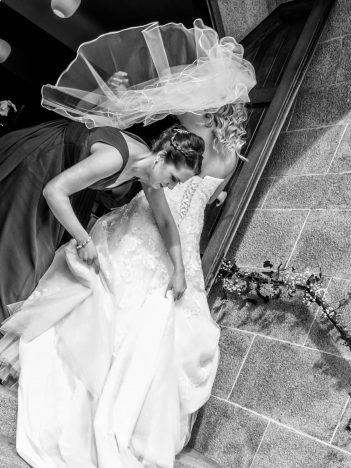 A black and white image of a bride arriving at the church with her hair blowing in the wind. A bridesmaid is helping pull her dress up the stairs