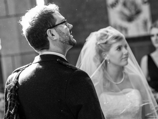 A bride and groom at the alter. The veil is cover the bride's face. The image is in black and white