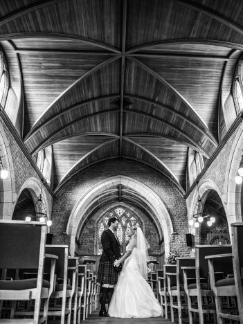 A black and white image of a bride and groom on their wedding day, standing in the middle of a church