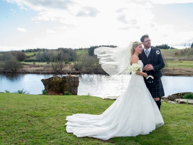 A bride and groom having their Maryculter House Hotel wedding photos in front of the river Dee