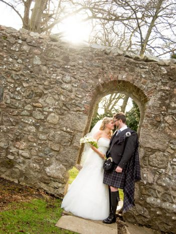 A bride and groom having their Maryculter House Hotel wedding photos in the grounds. The are standing below a stone arch