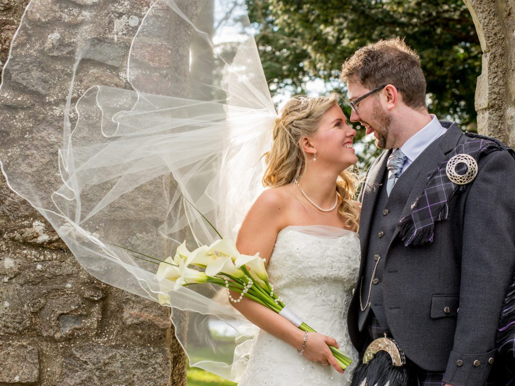 A bride and groom standing outside. The brides veil is flowing out behind her in the wind. She is wearing a strapless wedding dress and holding a bouquet of cala lillies. The groom is wearing a grey kilt