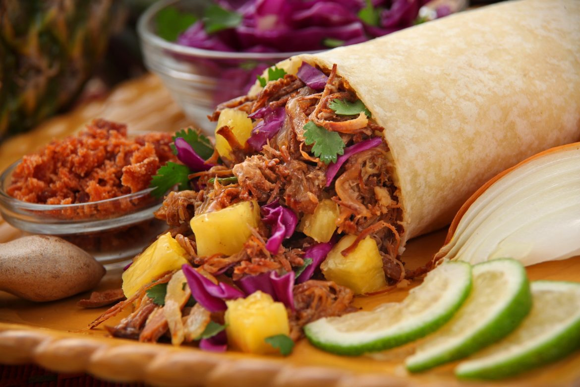 A pulled beef burrito with pineapple chunks, laid on a large board with lime wedges and condiments
