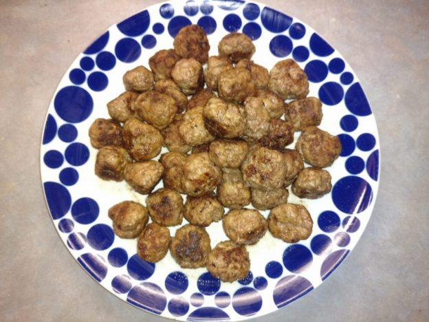 A spotted plate containing cooked homemade meatballs