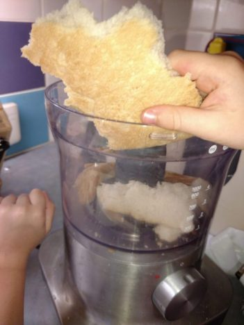 bread being put in to a food processor to make breadcrumbs