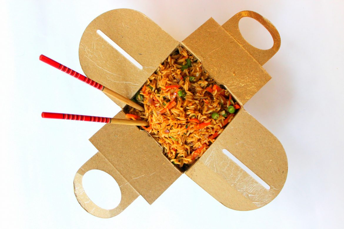 A takeaway container open with a Chinese dish inside and 2 chopsticks