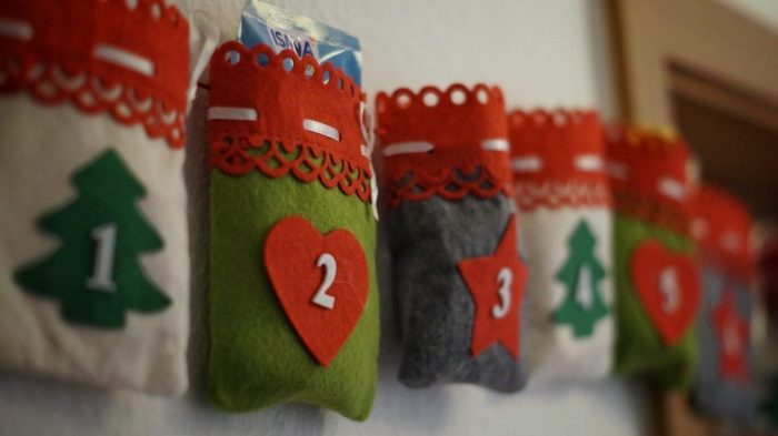 A white green and red fabric homemade advent calendar against a white wall