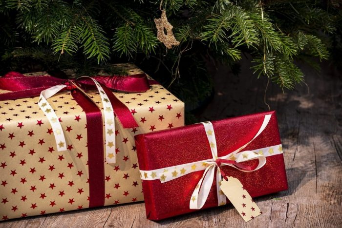2 Christmas presents under the tree wrapped in red and gold wrapping paper
