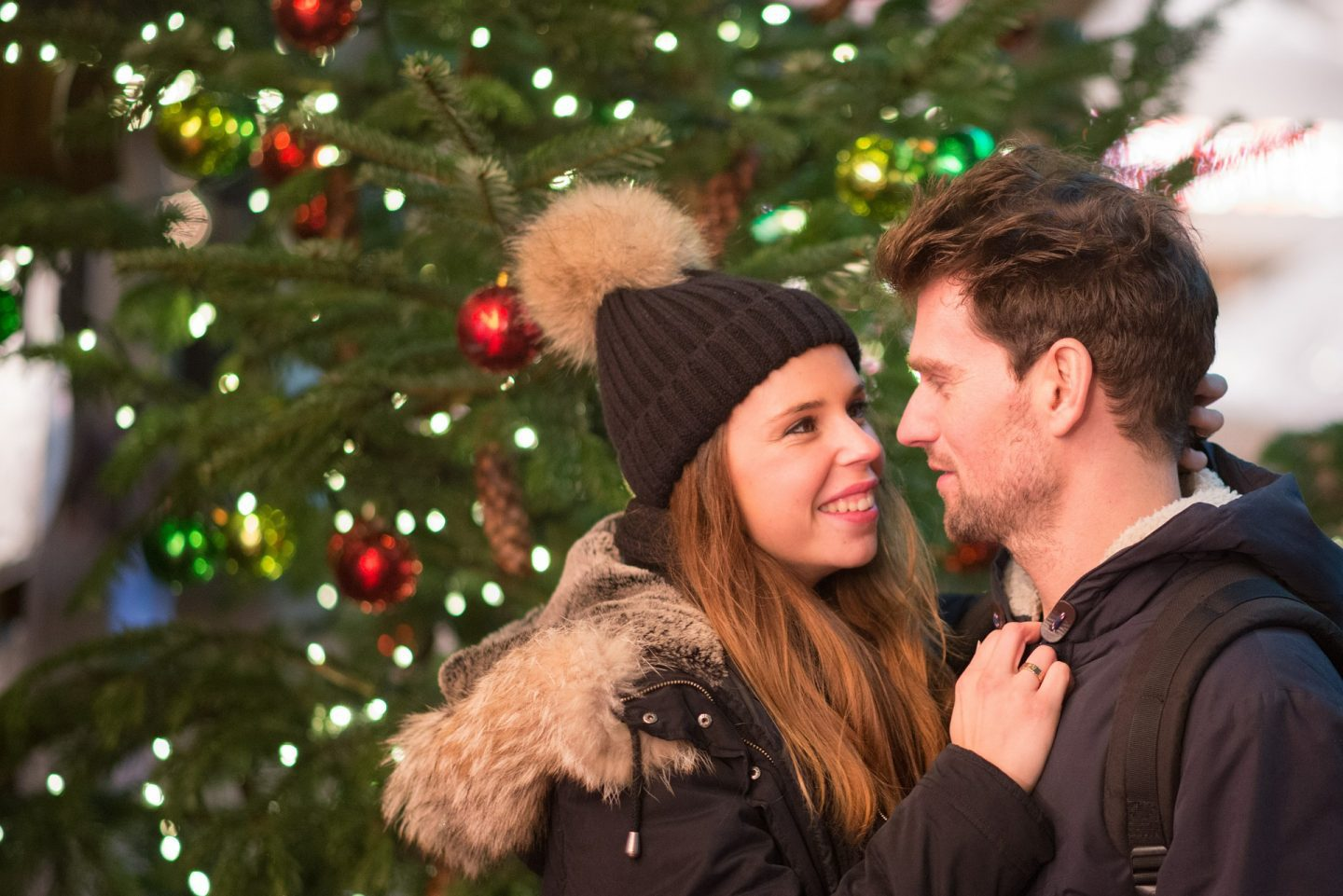 A man and a woman in a bobble hat are looking in to each others eyes in front of a Christmas tree.