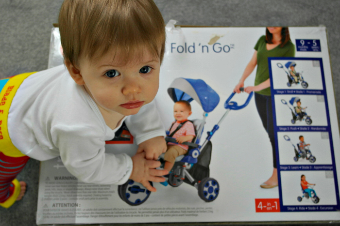A young boy climbing on top of a Little Tikes Fold 'n' Go 5-in-1 Trike box