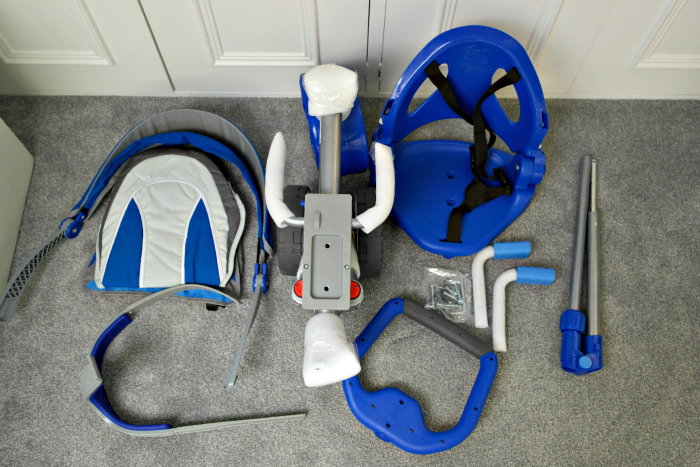 The blue parts of an unassembled push along trike