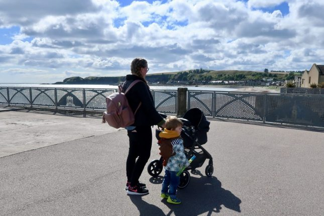 Maxi-Cosi Zelia Review | A mother and son walking by the harbour with a black pushchair www.oddhogg.com