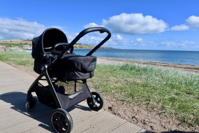 Maxi-Cosi Zelia Review | A black pushchairs next to the beach on a sunny day www.oddhogg.com