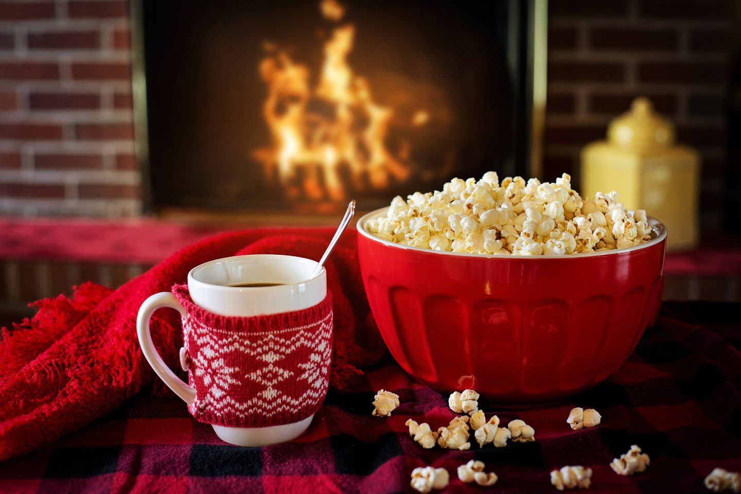 A white mug with a red and white knitted cover on it, next to a large red bowl full of popcorn with a large fire in the background