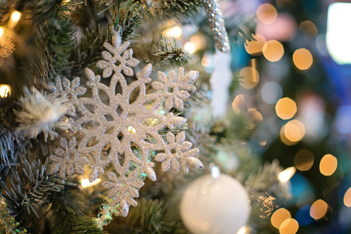 A close up of the branches of a Christmas tree with white snowflakes and baubles