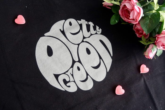 A close up of a black T-shirt with the pretty green logo on it. A bunch of roses is on the top right hand cover and a few red hearts lie scattered across it