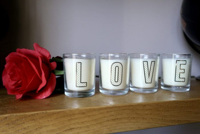 4 miniature candles that spell out LOVE and a single red rose