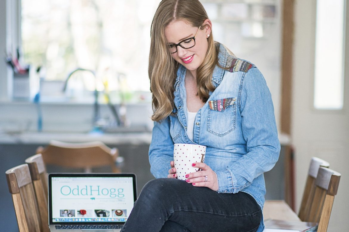 Pinterest Management Services | Woman sitting on the kitchen table wearing black jeans and a denim shirt. She is holding a white mug with gold polka dots on it. Next to her is an opten laptop www.oddhogg.com