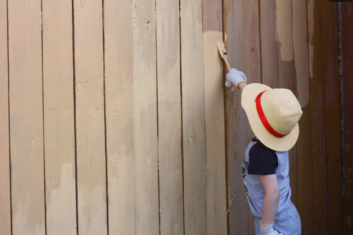 How To Prepare For Major Changes In Your Garden | A young boy wearing a hat with a red ribbon and a blue tshirt is painting a wooden fence a beige colour www.oddhogg.com