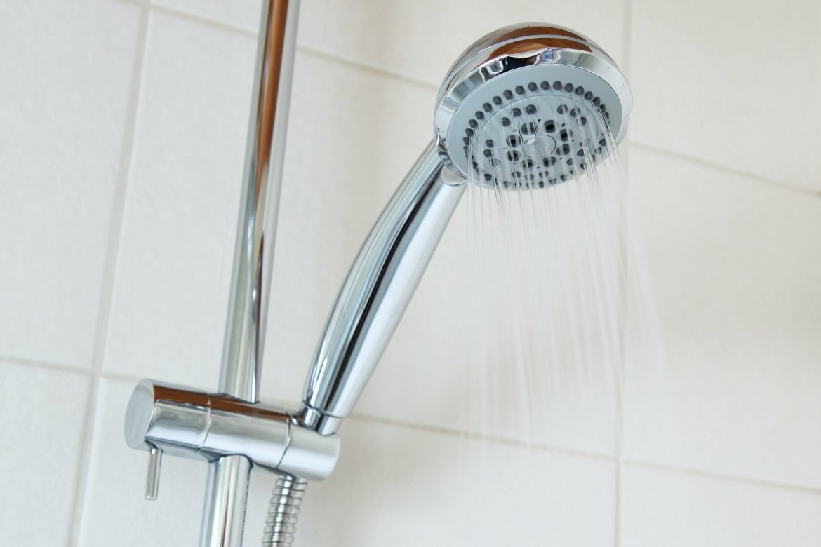 What Were Our Priorities In Our Home Renovation? | A chrome shower head with water coming out and a white tiled background www.oddhogg.com
