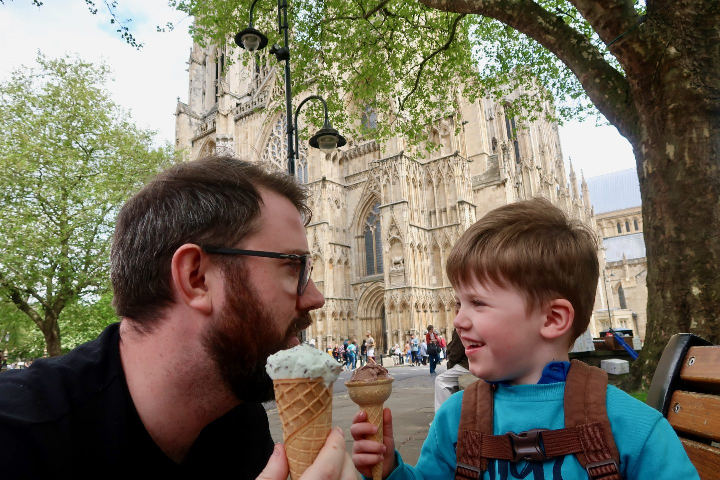 A young boy in a blue jumper is eating a chocolate ice cream with his father, eating a mint ice cream, in front of York Minister