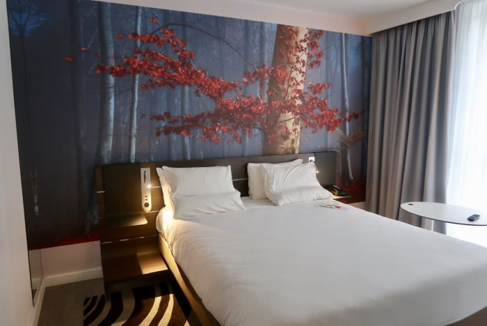 A double bed in a hotel room in Novotel York Centre, with a tree wallpaper behind it