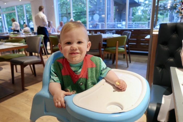 a young baby in a highchair at a restaurant. He is wearing a green and red bib