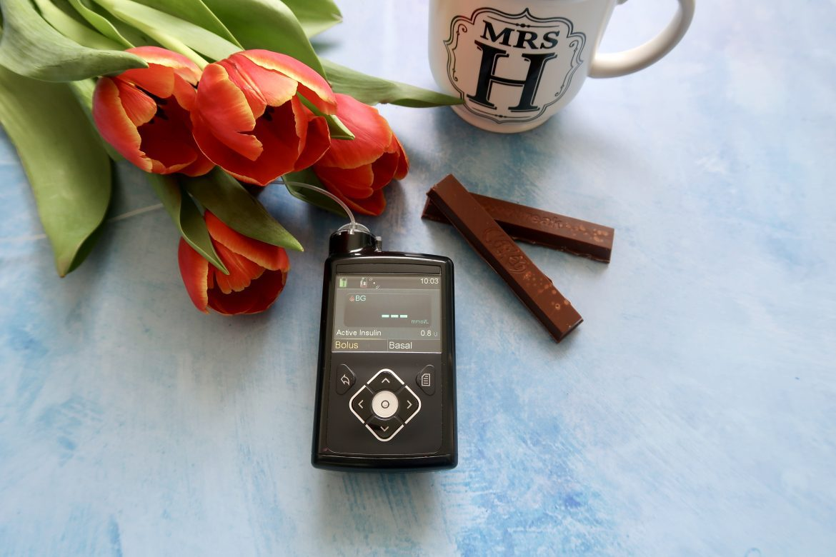 A pile of red tulips sits on a blue background with a mug with Mrs H written on it, a kit kat and an insulin pump