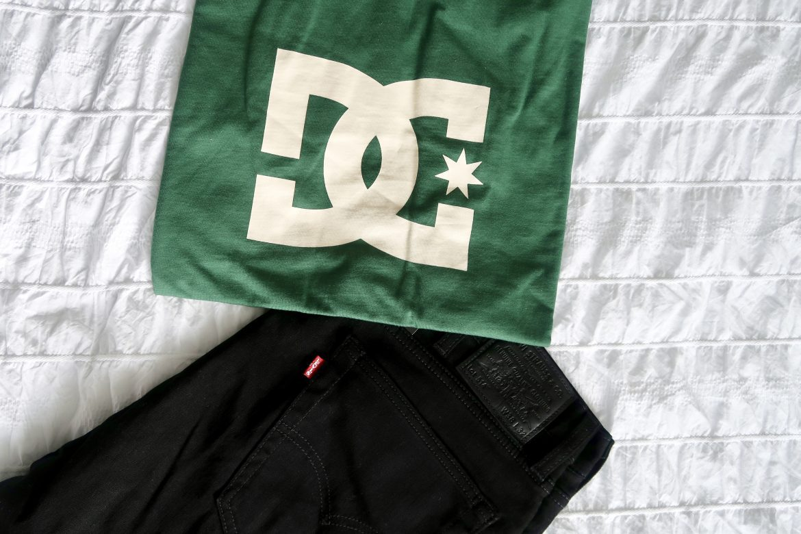 a green DC's tshirt with black Levi jeans lying on a bed