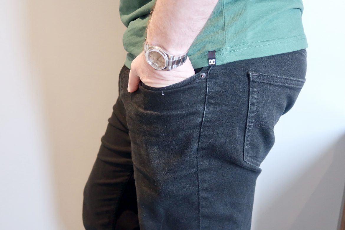 A man standing with his hand in his pocket. He is wearing balck Levi jeans and a green tshirt, with a rolex watch showing