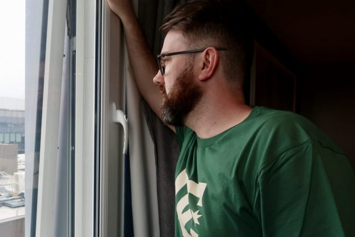 A man looking out of the window. He has glasses and a beard and is wearing a green tshirt