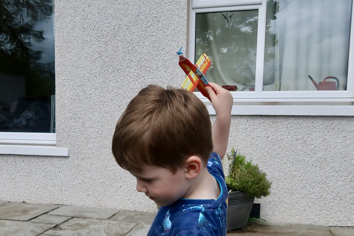 A young boy playing with a foam airplane in the garden