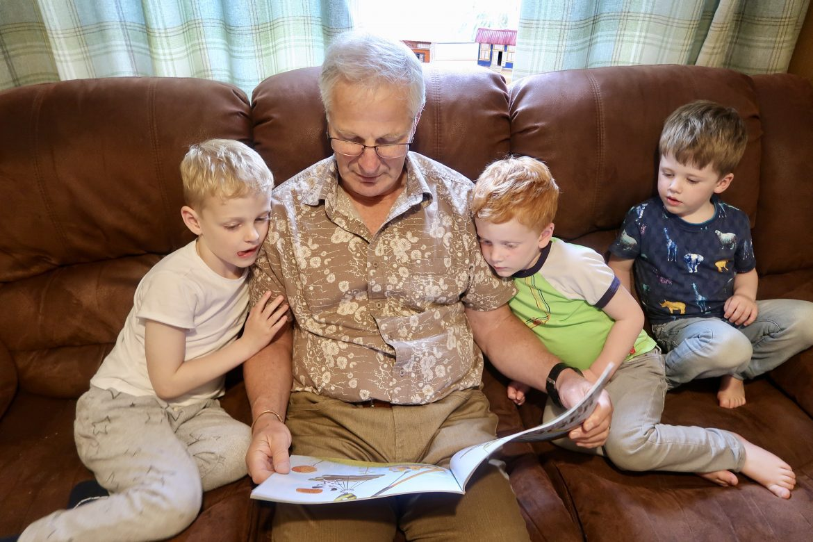 A grandfather reading a story to 3 of his grandsons