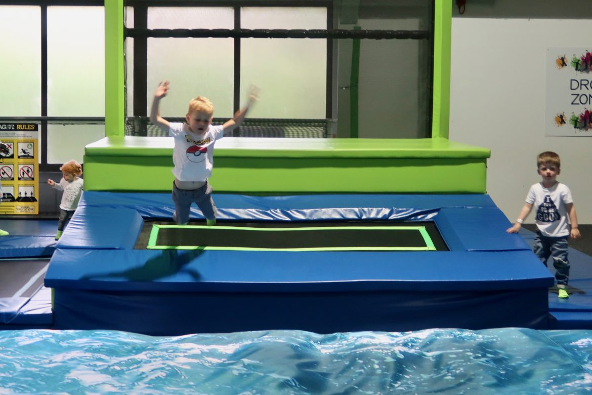 A boy jumping down from a ledge on to a trampoline, and then on to an air bag in a trampoline park