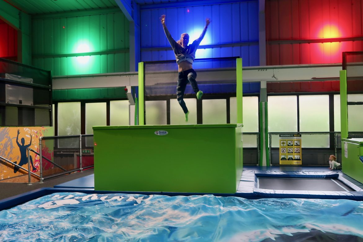 A woman jumping from a high green ledge, throwing her arms in the air