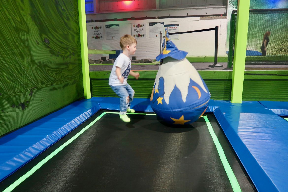 A young boy on a trampoline facing a giant soft toy wizard