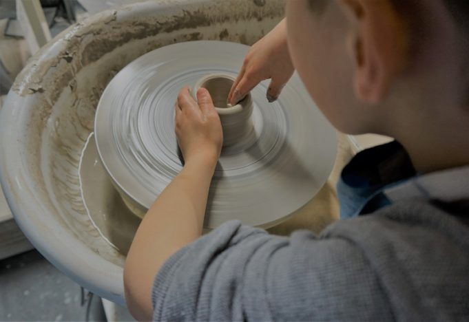 Looking down on a boy as he uses clay on a potters wheel