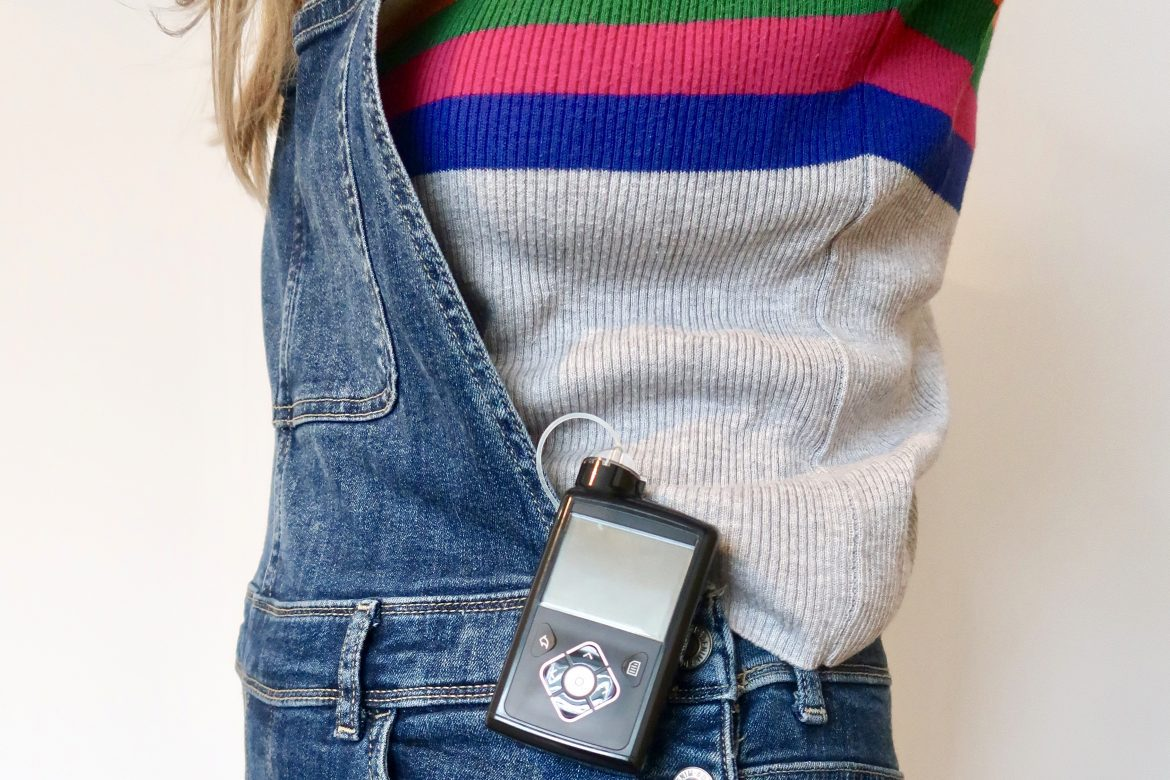 An insulin pump for type 1 diabetes clipped on to some dungarees over a rainbow and grey jumper