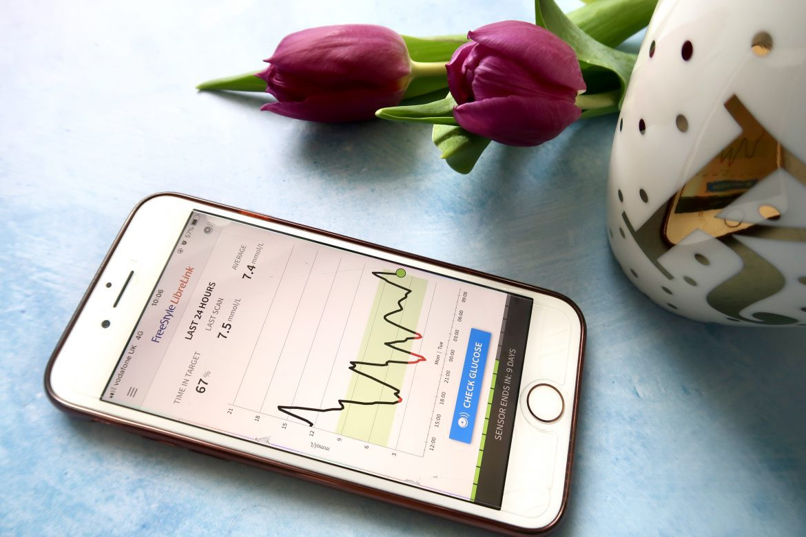 a phone with a freestyle libre graph on it, some purple tulips and a mug with gold spots and a letter K