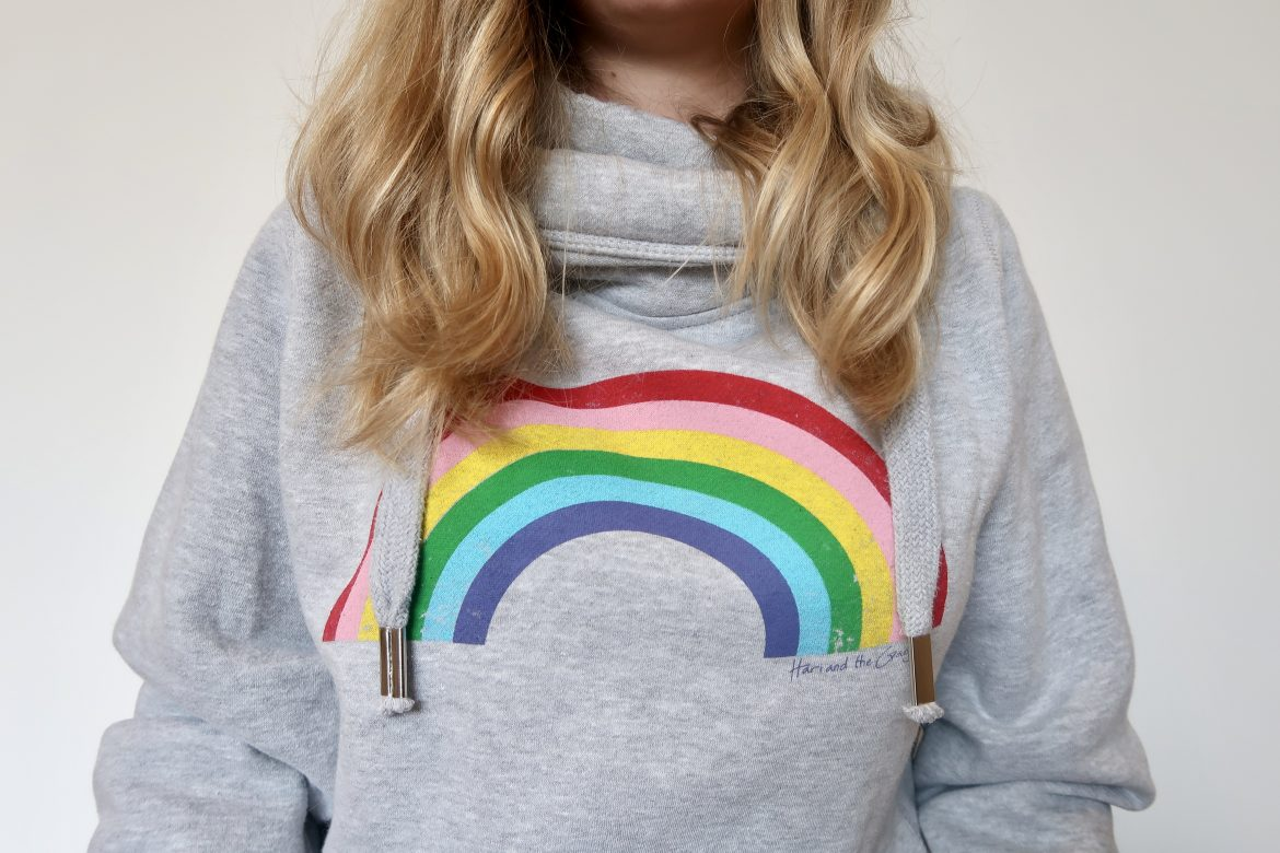 A rainbow hoodie on a woman with curly blonde hair