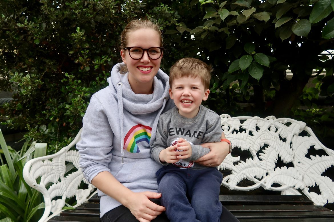 A woman wearing a grey Hari and the Gang hoodie with a rainbow on it, sitting on a white bench and hugging her son