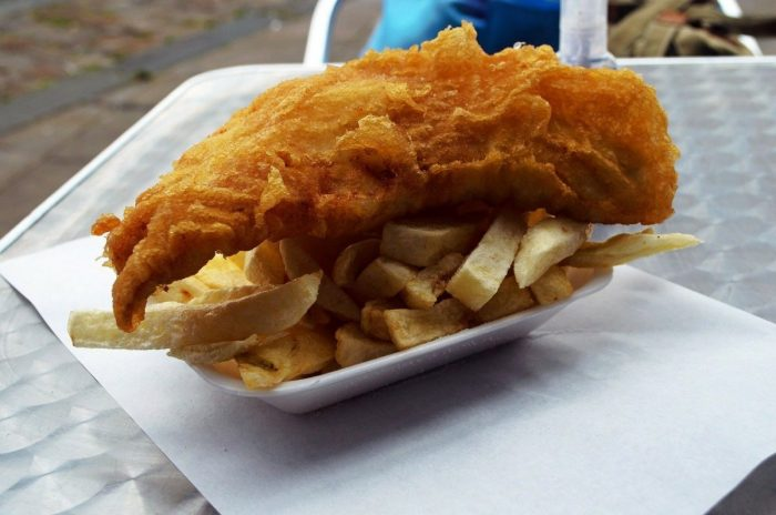 a takeaway dish of fish and chips on a metal outdoor table