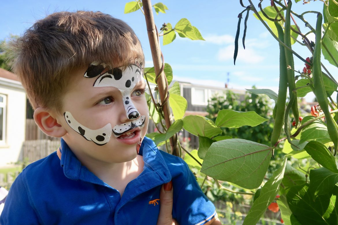 A boy looking at a plant with his face painted like a dog