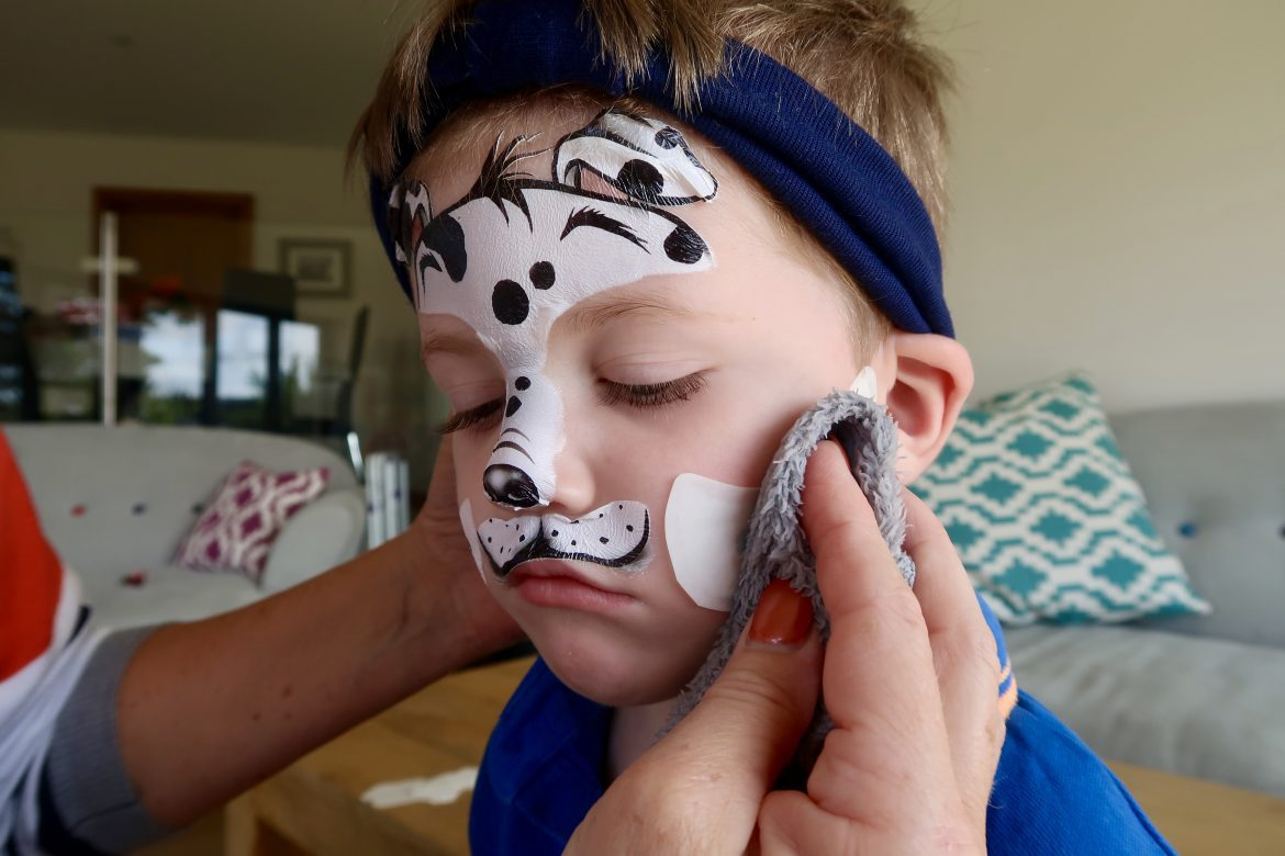 A boy having dalmation face paintoos applied