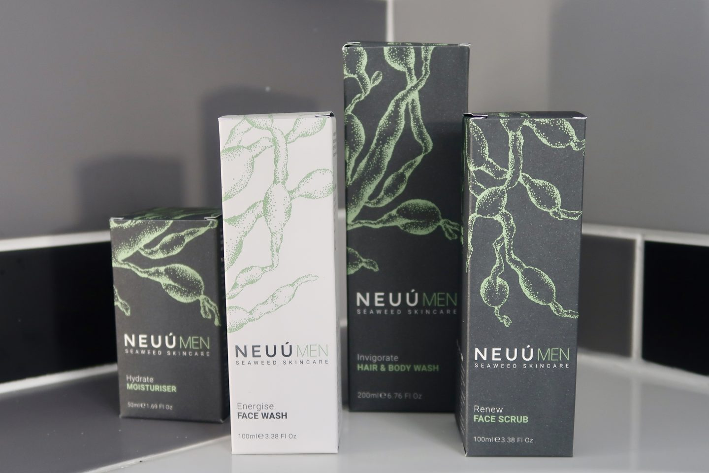 4 boxes of NEUU skincare products. 3 boxes are dark grey with green leaves design, one is white with the same green leaf design