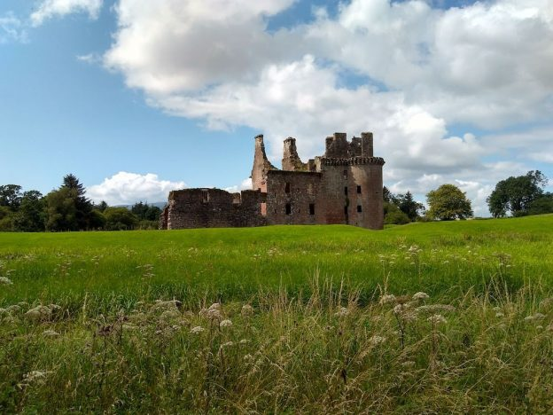 Caerlaverock Castle in Dumfries set at the back of the photo with a large lawn in the foreground