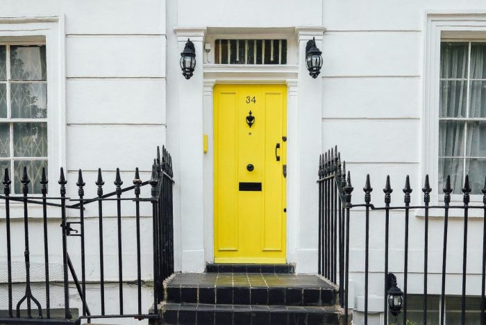 a white building with a bright yellow front door