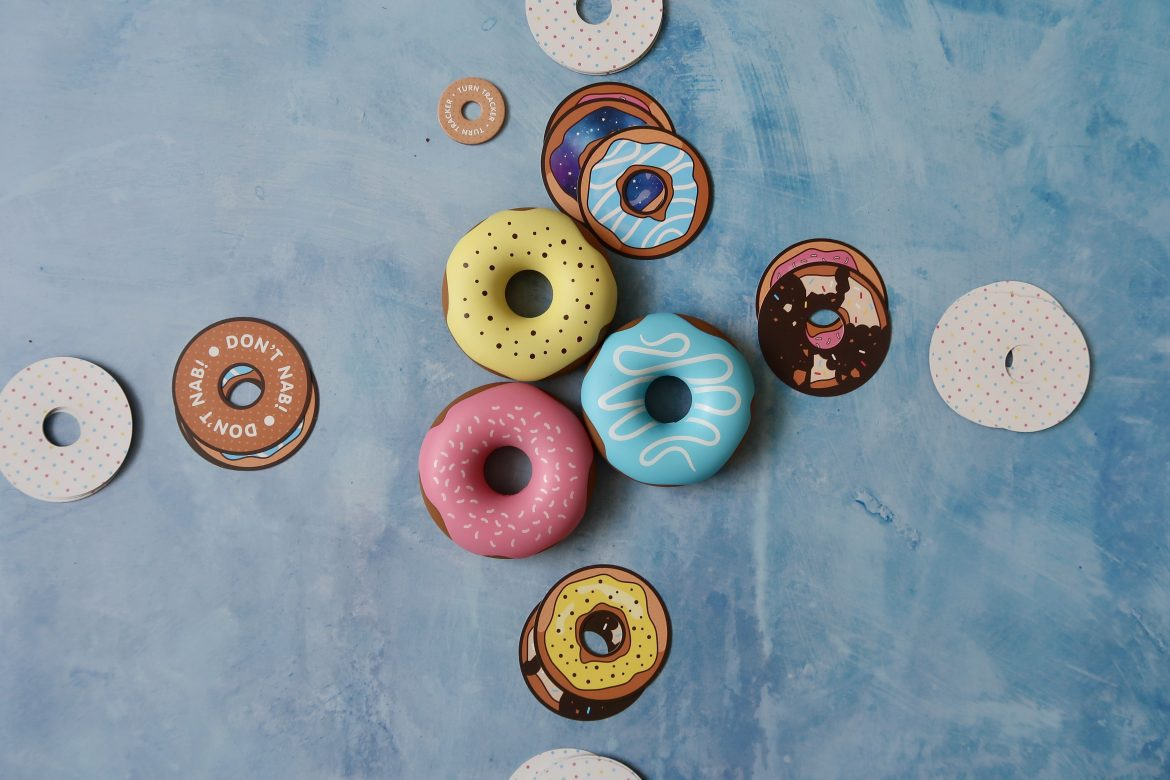 Plastic donuts and donut cards laid out as park of the Dough Nab game
