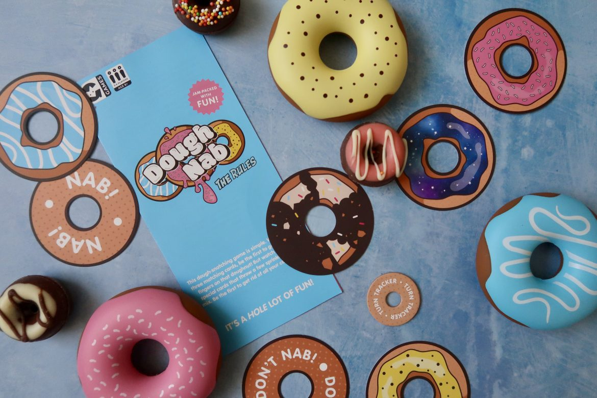 An array of multicoloured donuts as part of the Dough Nab Game, as well as the game instructions. Some of the donuts are plastic, some are cards and some are made from chocolate